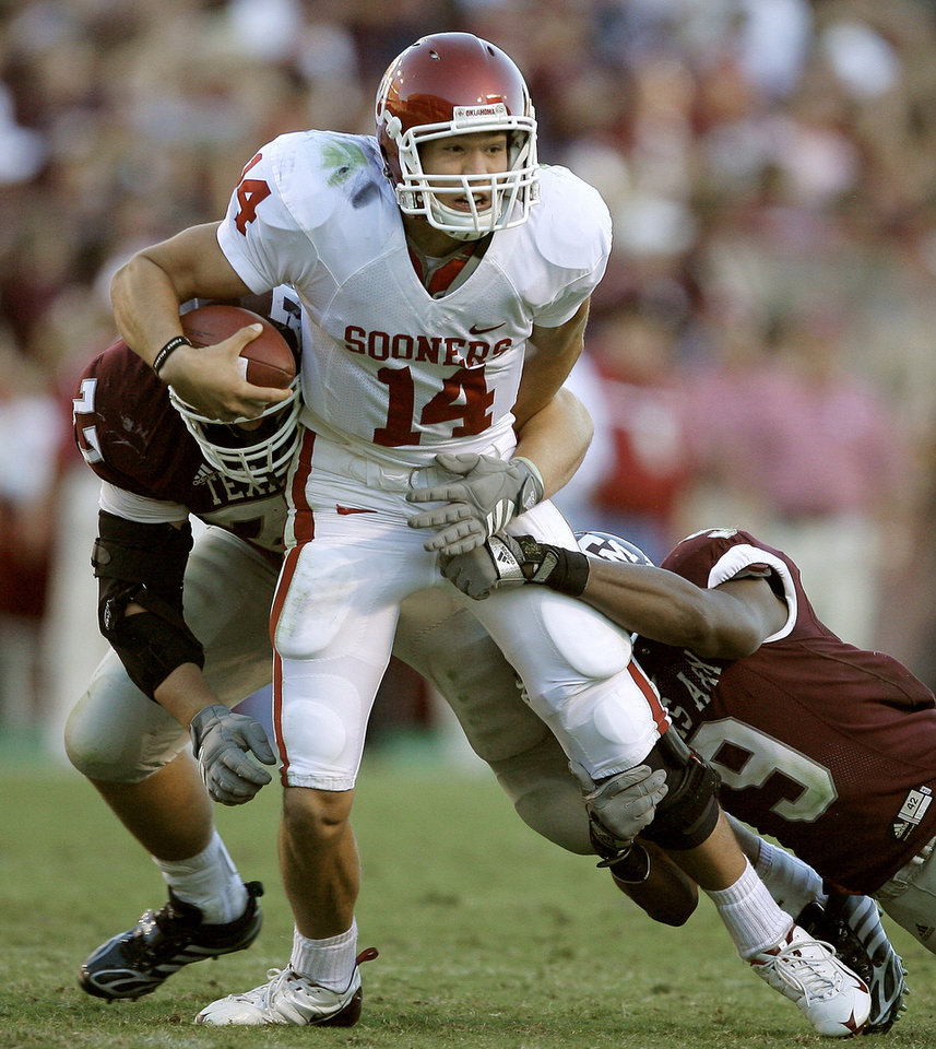 Photo - OU's Sam Bradford fights off Lucas Patterson, left, and Alton Dixon of Texas A&M during the college football game between the University of Oklahoma and Texas A&M University at Kyle Field in College Station, Texas, Saturday, November 8, 2008.  BY BRYAN TERRY, THE OKLAHOMAN