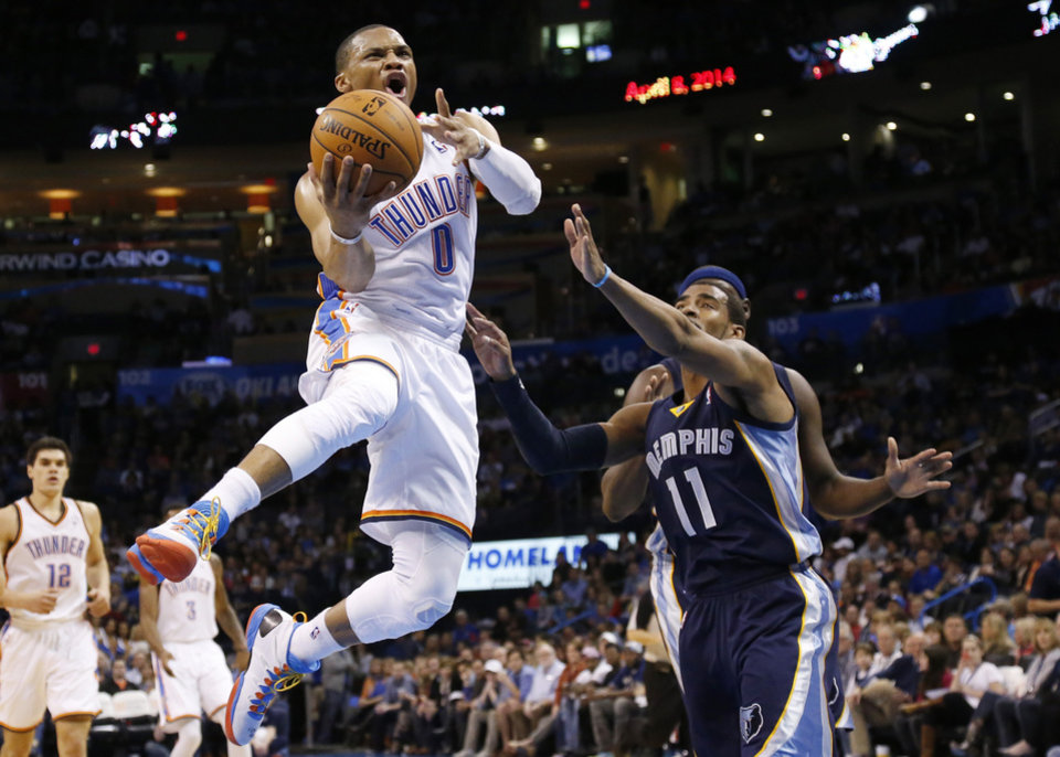 Photo - Oklahoma City Thunder guard Russell Westbrook (0) goes up for a shot in front of Memphis Grizzlies guard Mike Conley (11) during the third quarter of an NBA basketball game in Oklahoma City, Friday, Feb. 28, 2014. Oklahoma City won 113-107. (AP Photo/Sue Ogrocki)