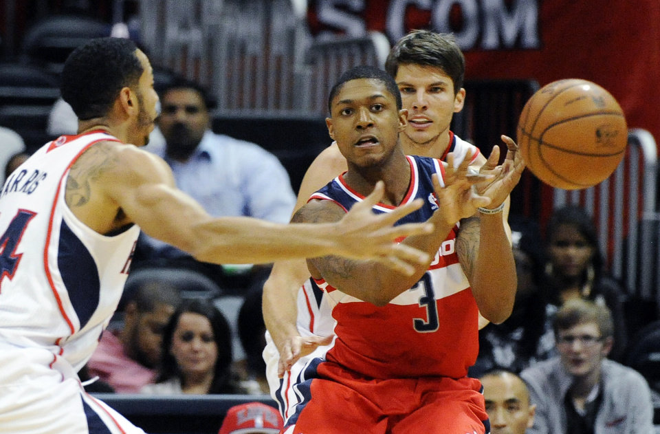 Washington Wizards' Bradley Beal (3) passes around Atlanta Hawks' Devin Harris (34) and Kyle Korver in the first half of an NBA basketball game at Philips Arena in Atlanta, Wednesday, Nov. 21, 2012. (AP Photo/David Tulis)