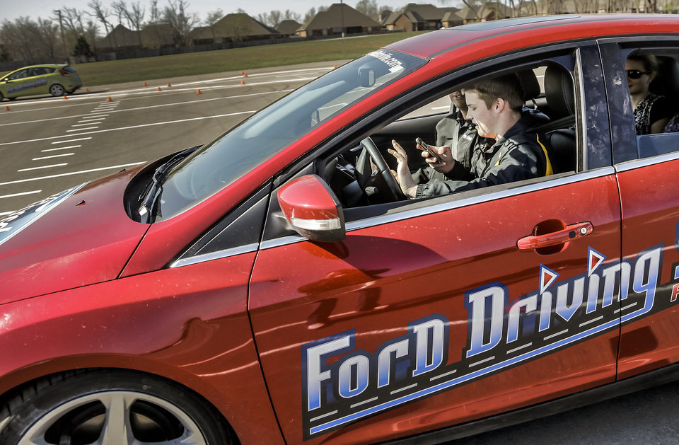 Collin Spangler tries to text and drive while navigating a course during the Ford Driving Skills For Life interactive course at Yukon High School on Thursday, April 111, 2013, in Yukon, Okla. Photo by Chris Landsberger, The Oklahoman