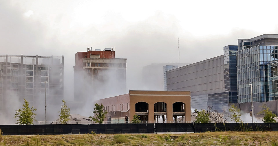 Photo - The view as the cloud of dust begins to settle after the Hotel Black and adjoining parking garage in downtown Oklahoma City are taken down during an implosion by Midwest Wrecking Company on Sunday, Sept. 13, 2015, in Oklahoma City, Okla.  Photo by Chris Landsberger, The Oklahoman