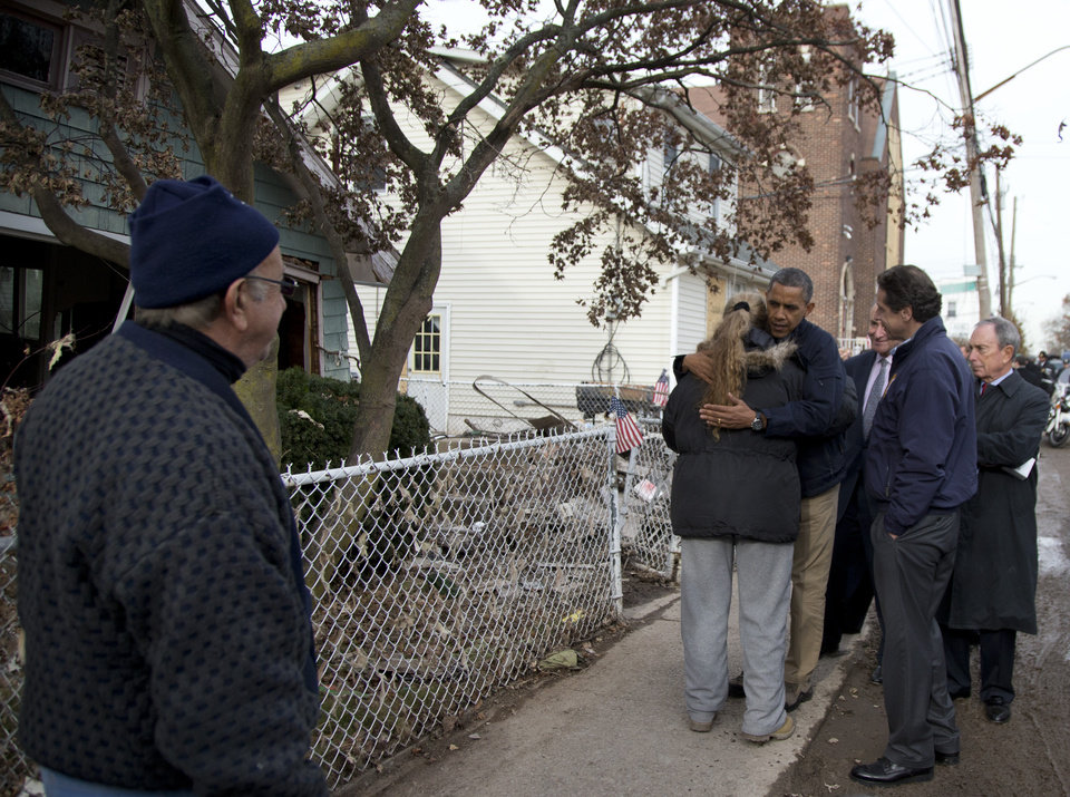 Photo -   President Barack Obama, accompanied by New York City Mayor Michael Bloomberg, New York Gov. Andrew Cuomo and Sen. Charles Schumer, D-N.Y., hugs Debbie Ingenito on Cedar Grove Avenue, a street significantly impacted by Superstorm Sandy, Thursday, Nov. 15, 2012, on Staten Island, in New York. (AP Photo/Carolyn Kaster)