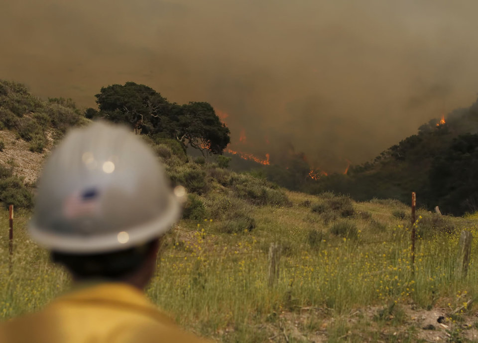 Photo - A fire fighter watches the fast moving Miguelito Fire along San Miguelito Rd Tuesday May 13, 2014. Wildfires pushed by gusty winds chewed through canyons parched by California's drought, prompting evacuation orders for 1,200 homes and businesses in Santa Barbara County. (AP Photo/The Santa Maria Times, Daniel Dreifuss)