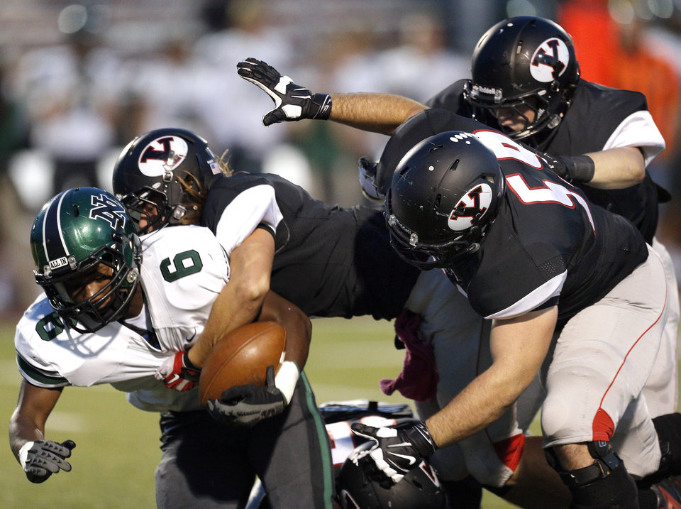 Norman North's Z'Quan Hogan is tackled by a group of Yukon defenders during a high school football game between Yukon and Norman North in Yukon, Okla.,   Friday, Oct. 4, 2013. Photo by Sarah Phipps, The Oklahoman