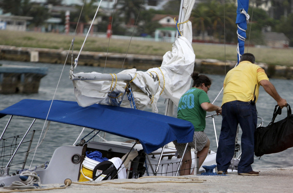 Photo - Sharyn Hakken is helped out of her boat by a safety officer at the Hemingway Marina in Havana, Cuba, Tuesday, April 9, 2013. Sharyn and her husband Joshua Michael Hakken, who had lost custody of their two young boys, allegedly kidnapped them from Sharyn's parents in Florida and fled by boat to Havana. A foreign ministry official told The Associated Press in a written statement Tuesday that Cuba had informed U.S. authorities of the country's decision to turn over Hakken, his wife and their two young boys. She did not say when the handover would occur. (AP Photo/Franklin Reyes)
