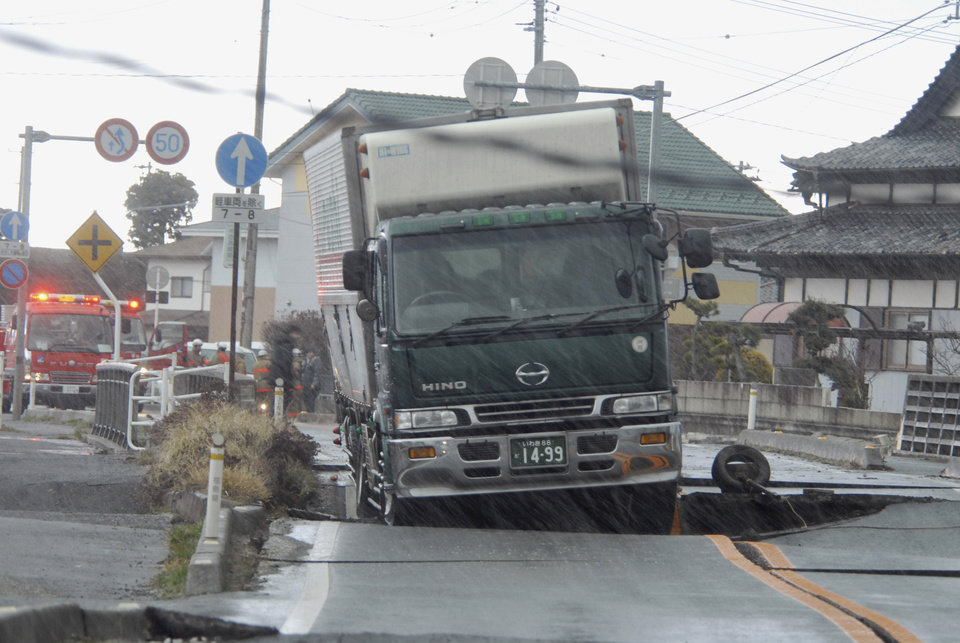 Photo - A truck remains stranded on a road damaged by a powerful earthquake in Iwaki city, Fukushima prefecture (state), Japan, Friday, March 11, 2011. The largest earthquake in Japan's recorded history slammed the eastern coast Friday. (AP Photo/Kyodo News) JAPAN OUT, MANDATORY CREDIT, FOR COMMERCIAL USE ONLY IN NORTH AMERICA ORG XMIT: TTX803