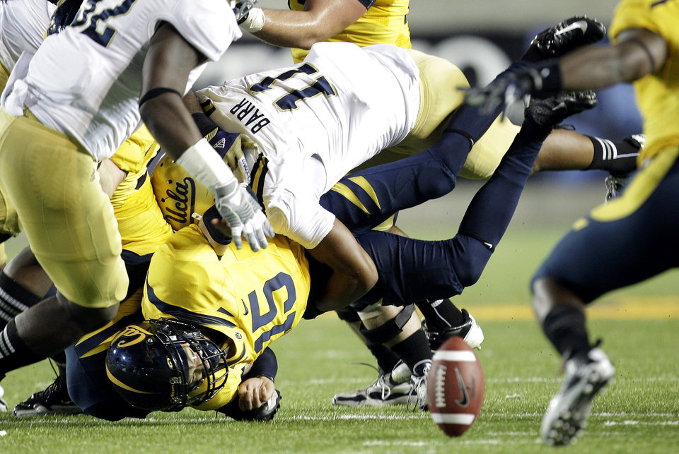 Photo -   California quarterback Zach Maynard (15) fumbles the ball as he is sacked by UCLA linebacker Anthony Barr (11) during the first half of an NCAA college football game in Berkeley, Calif., Saturday, Oct. 6, 2012. California recovered the ball. (AP Photo/Tony Avelar)