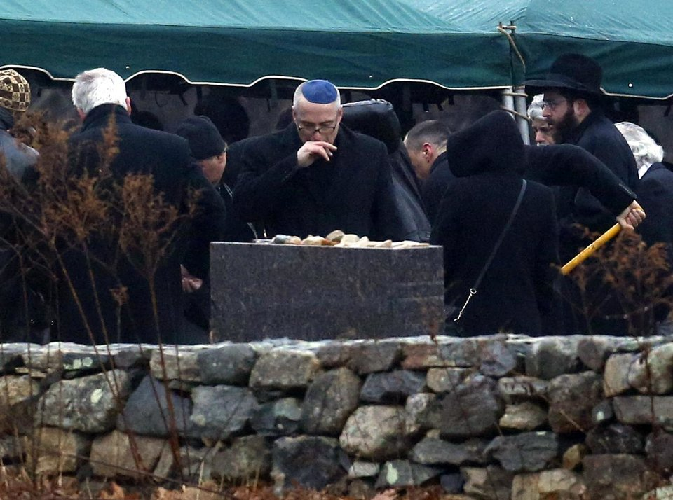 A man, center, reacts while others shovel dirt onto the grave of Noah Pozner, a six-year-old killed in the Sandy Hook Elementary School shooting, was laid to rest at B'nai Israel Cemetery, Monday, Dec. 17, 2012, in Monroe, Conn. Authorities say gunman Adam Lanza killed his mother at their home on Friday and then opened fire inside the Sandy Hook Elementary School in Newtown, killing 26 people, including 20 children, before taking his own life. (AP Photo/Julio Cortez) ORG XMIT: CTJC129