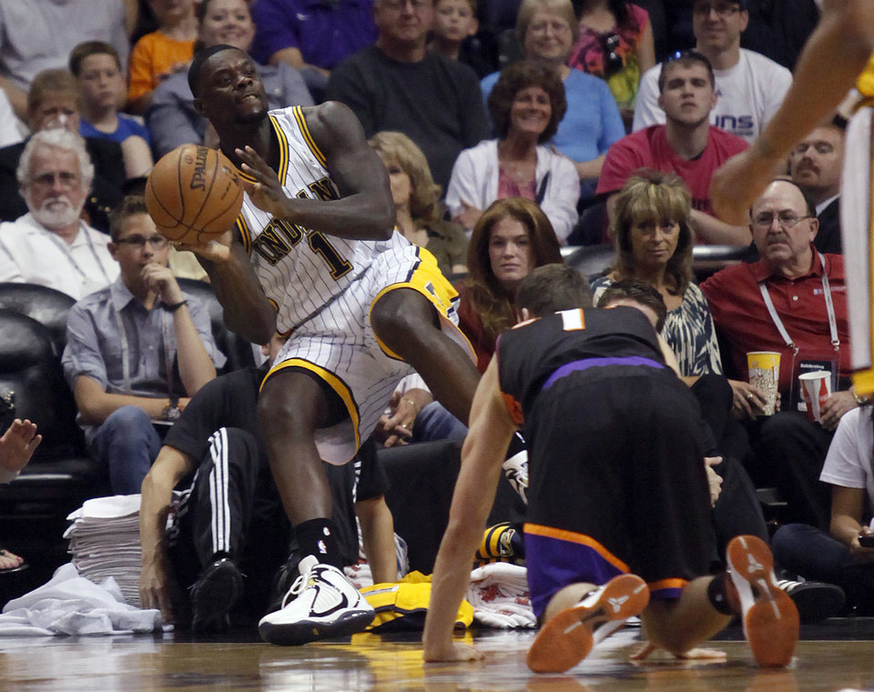 Photo - Indiana Pacers guard Lance Stephenson, left, throws the ball into play as he tumbles out out bounds and Phoenix Suns guard Goran Dragic, right, of Slovenia, looks on during the first half of an NBA basketball game Saturday, March 30, 21013, in Phoenix. (AP Photo/Paul Connors)