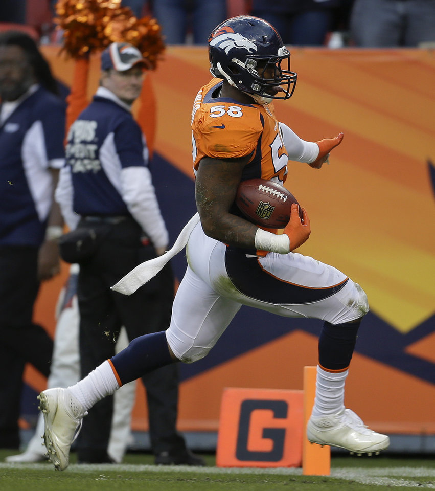 Photo - Denver Broncos outside linebacker Von Miller (58) crosses the goal line for a touchdown after intercepting a pass against the Tampa Bay Buccaneers in the third quarter of an NFL football game, Sunday, Dec. 2, 2012, in Denver. (AP Photo/Joe Mahoney)