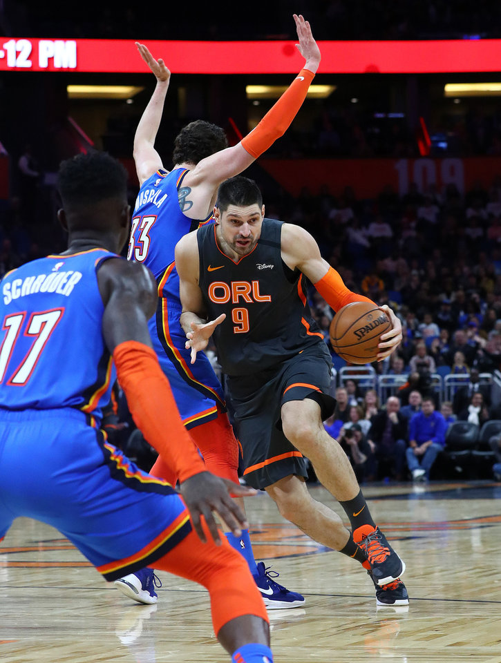Photo - Jan 22, 2020; Orlando, Florida, USA; Orlando Magic center Nikola Vucevic (9) drives to the basket as Oklahoma City Thunder forward Mike Muscala (33) defends during the second half at Amway Center. Mandatory Credit: Kim Klement-USA TODAY Sports