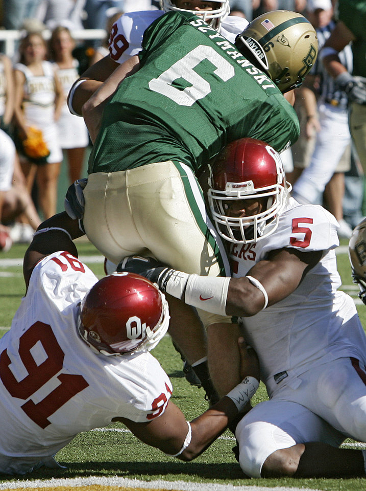 Photo - Oklahoma's Alonzo Dotson (91) and Nic Harris (5) bring Baylor quarterback Blake Szymanski (6) down for a safety in the second half during the University of Oklahoma Sooners (OU) college football game against Baylor University Bears (BU) at Floyd Casey Stadium, on Saturday, Nov. 18, 2006, in Waco, Texas.     by Chris Landsberger, The Oklahoman