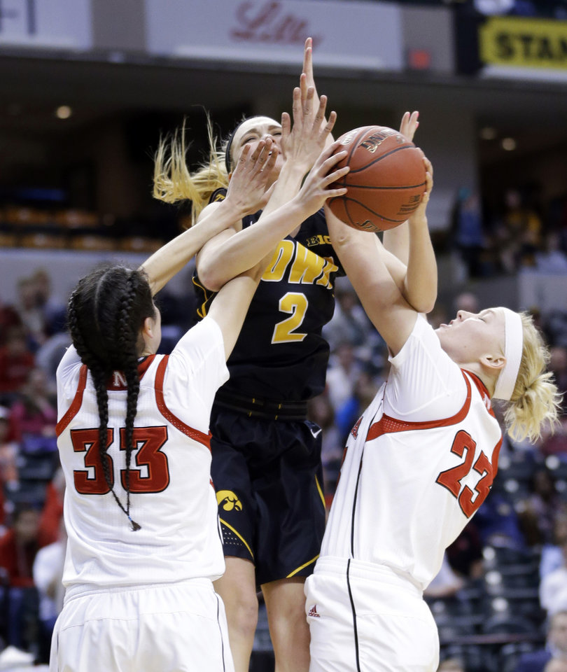 Photo - Iowa guard Ally Disterhoft (2) is fouled by Nebraska guard Rachel Theriot (33) and forward Emily Cady in the first half of an NCAA college basketball game in the finals of the Big Ten women's tournament in Indianapolis, Sunday, March 9, 2014. (AP Photo/Michael Conroy)