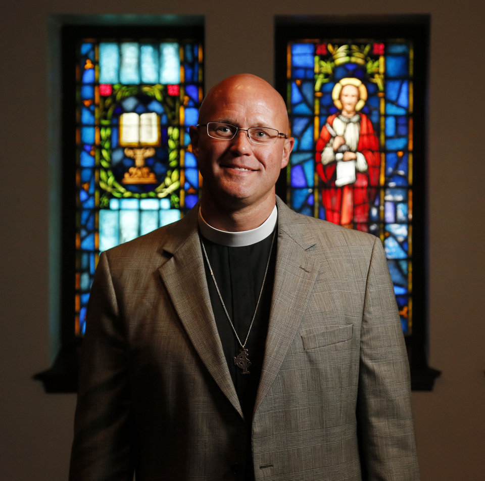 Photo - The Rev. Justin Lindstrom, the new dean at St. Paul's Episcopal Cathedral, poses for a photo in the sanctuary of the historic downtown Oklahoma City church, 127 NW 7.   NATE BILLINGS - NATE BILLINGS