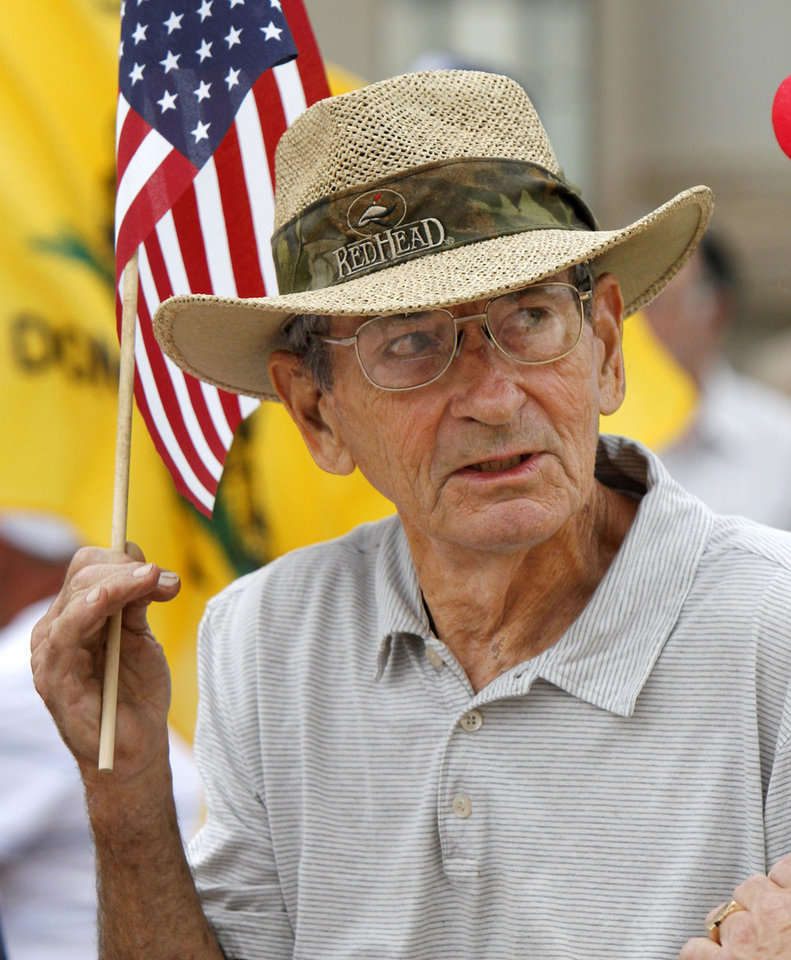 Photo - Don Beighle holds a flag Saturday during a health care law protest on the south steps of the state  Capitol building.