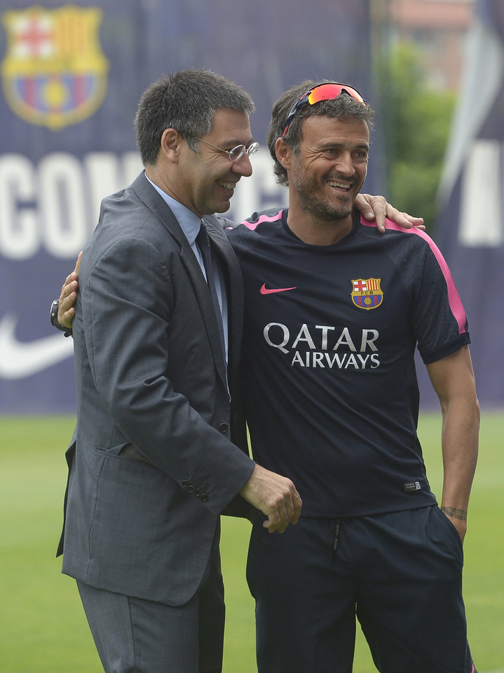 Photo - FC Barcelona's president Josep Maria Bartomeu, left, embraces head coach Luis Enrigue prior to a training session at the Sports Center FC Barcelona Joan Gamper in San Joan Despi, Spain, Friday, July 25, 2014. (AP Photo/Manu Fernandez)