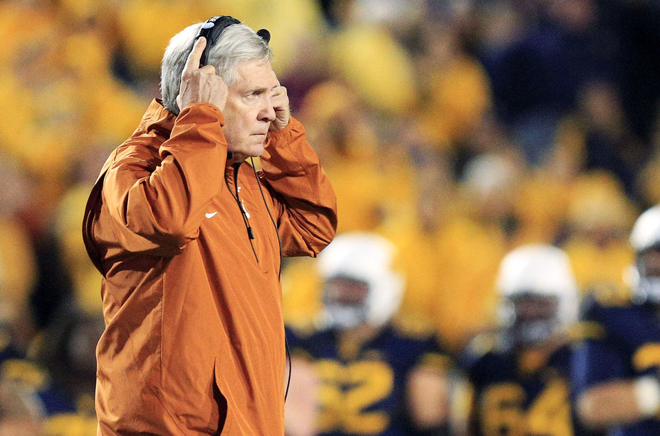 Photo - Texas coach Mack Brown walks across the field after an injury to one of his players in the second quarter of an NCAA college football game against West Virginia in Morgantown, W.Va., on Saturday, Nov. 9, 2013. Texas won 47-40 in overtime. (AP Photo/Christopher Jackson)