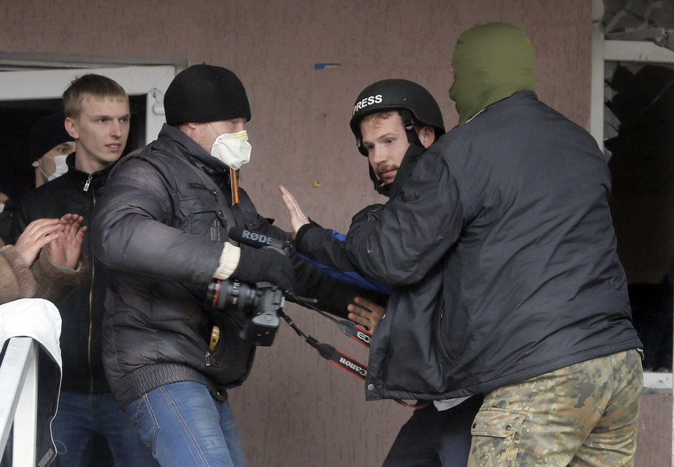 Photo - Masked pro-Russian men attack British photojournalist Frederick Paxton, 2nd right, during the mass storming of a police station in the eastern Ukrainian town of Horlivka Monday, April 14, 2014.  Several government buildings has fallen to mobs of Moscow loyalists in recent days as unrest spreads across the east of the country. Western journalists have routinely been targeted for intimidation by crowds during the stormings. (AP Photo/Efrem Lukatsky)