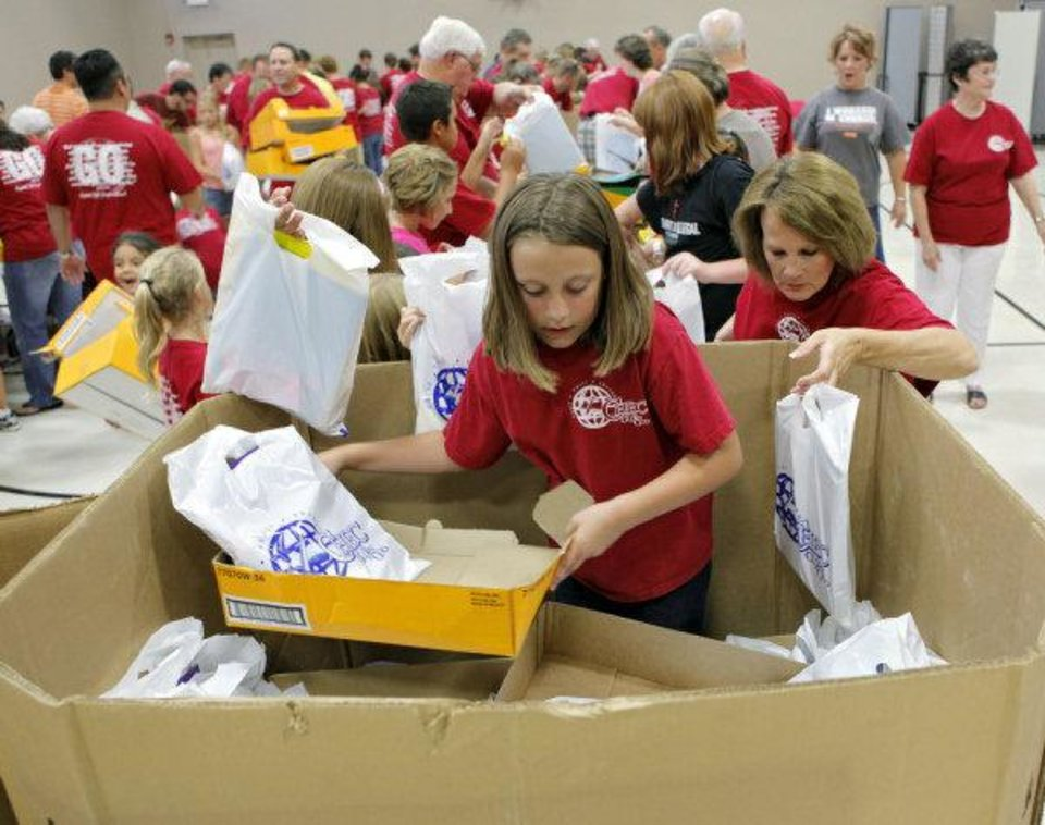 Photo - Indigo Harkness, 11, and other members of Capitol Hill Baptist Church in south Oklahoma City, fill bags and boxes with school supplies for the church's carnival and school supply give-away set for Sunday.   JOHN CLANTON - John Clanton