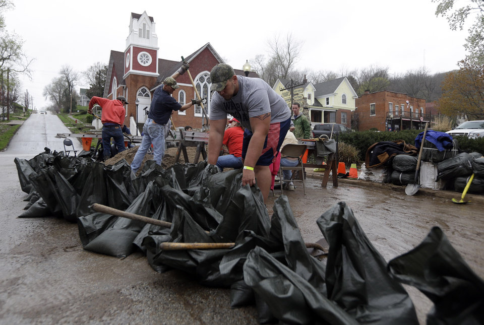 Photo - Steve Dieckhaus arranges sand bags being filled in hopes of holding back the rising Mississippi River Thursday, April 18, 2013, in Clarksville, Mo. Middle America was overwhelmed by weather Thursday, with snow in the north, tornadoes in the Plains, and torrential rains that caused floods and transportation woes (AP Photo/Jeff Roberson)
