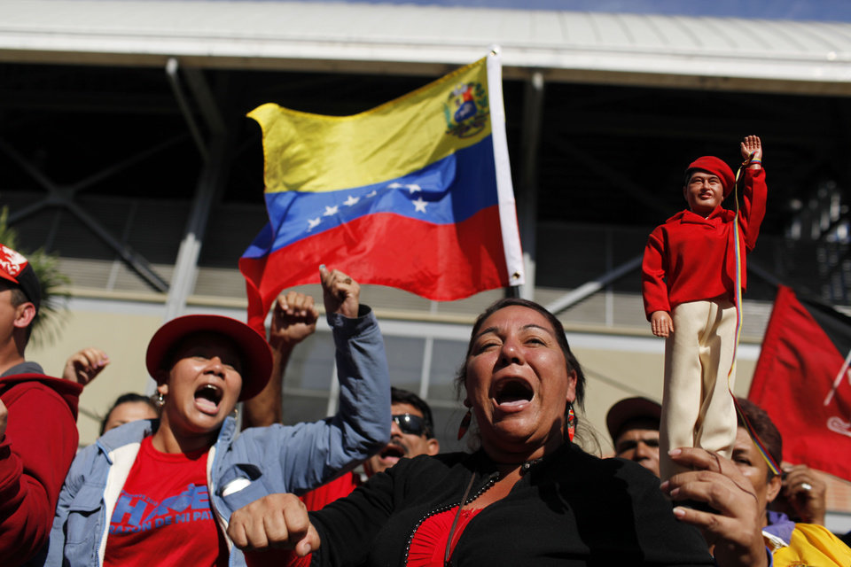 Supporters of Venezuela's late President Hugo Chavez shout slogans as they line up outside the military academy where a funeral ceremony will take place for him in Caracas, Venezuela, Friday, March 8, 2013. At right, a Chavez supporter holds up a doll in his likeness.  Friday's funeral promises to be a final turn on the world stage for Chavez after 14 years in power, though in some ways the former paratrooper is not going anywhere: Venezuela announced Thursday that it would embalm his body and put it on permanent display. Chavez died on March 5 after a nearly two-year bout with cancer. He was 58. (AP Photo/Rodrigo Abd)