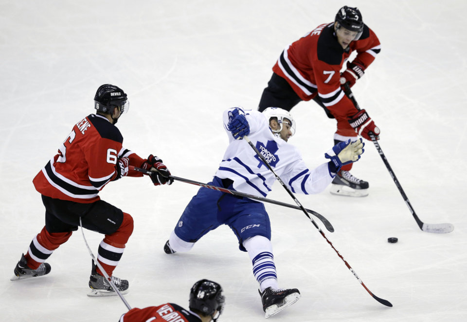 Photo - Toronto Maple Leafs' Nazem Kadri (43) is hit by New Jersey Devils' Andy Greene (6) as Devils' Mark Fayne (7) goes for the puck during the second period of an NHL hockey game, Sunday, March 23, 2014, in Newark, N.J. (AP Photo/Mel Evans)