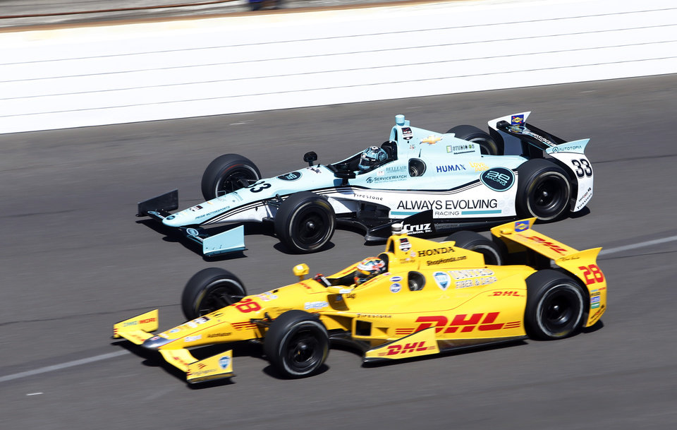 Photo - Ryan Hunter-Reay, bottom and James Davison, of Australia, head into the first turn on the final day of practice for the Indianapolis 500 IndyCar auto race at the Indianapolis Motor Speedway in Indianapolis, Friday, May 23, 2014. The 98th running of the Indianapolis 500 is Sunday. (AP Photo/Tom Strattman)