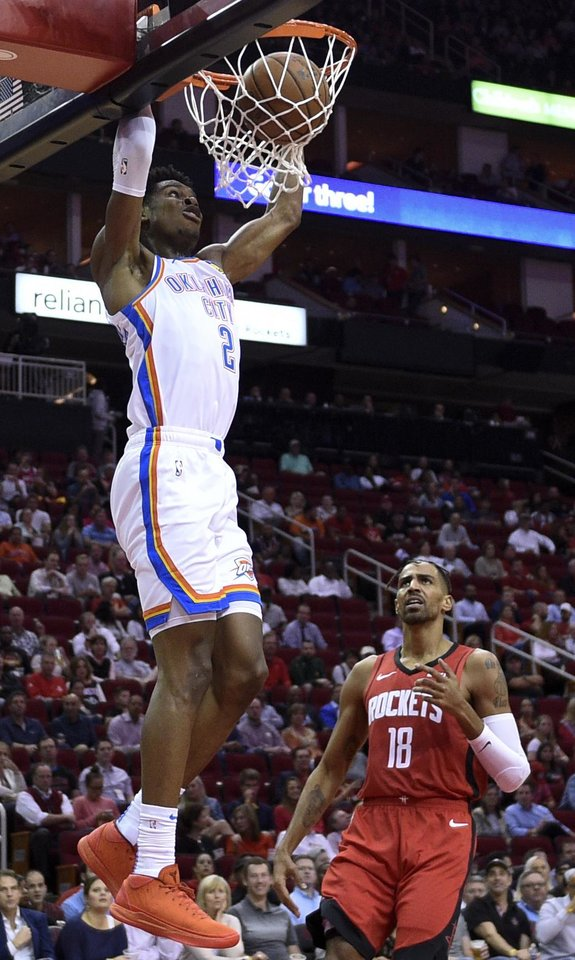 Photo - Oklahoma City Thunder guard Shai Gilgeous-Alexander (2) dunks as Houston Rockets forward Thabo Sefolosha watches during the first half of an NBA basketball game, Monday, Oct. 28, 2019, in Houston. (AP Photo/Eric Christian Smith)
