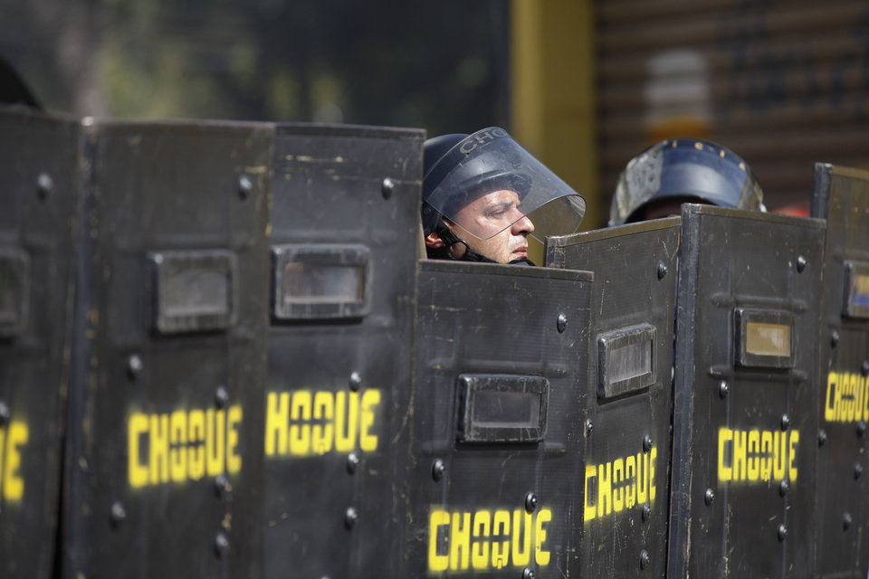 Photo - A Brazilian riot policeman looks up from behind his shield after clashes erupted in Sao Paulo, Brazil, Thursday, June 12, 2014. More than 300 demonstrators gathered along a main highway leading to the stadium. Some in the crowd tried to block traffic, but police repeatedly pushed them back, firing canisters of tear gas and using stun grenades. (AP Photo/Dario Lopez-Mills)