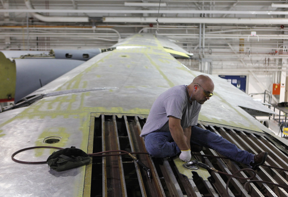TINKER MAINTENANCE FACILITIES: Javan Cutter works on the wing of a KC-135 at Tinker Air Force Base in Midwest City, Tuesday, July 3, 2012.  The Oklahoman Archives
