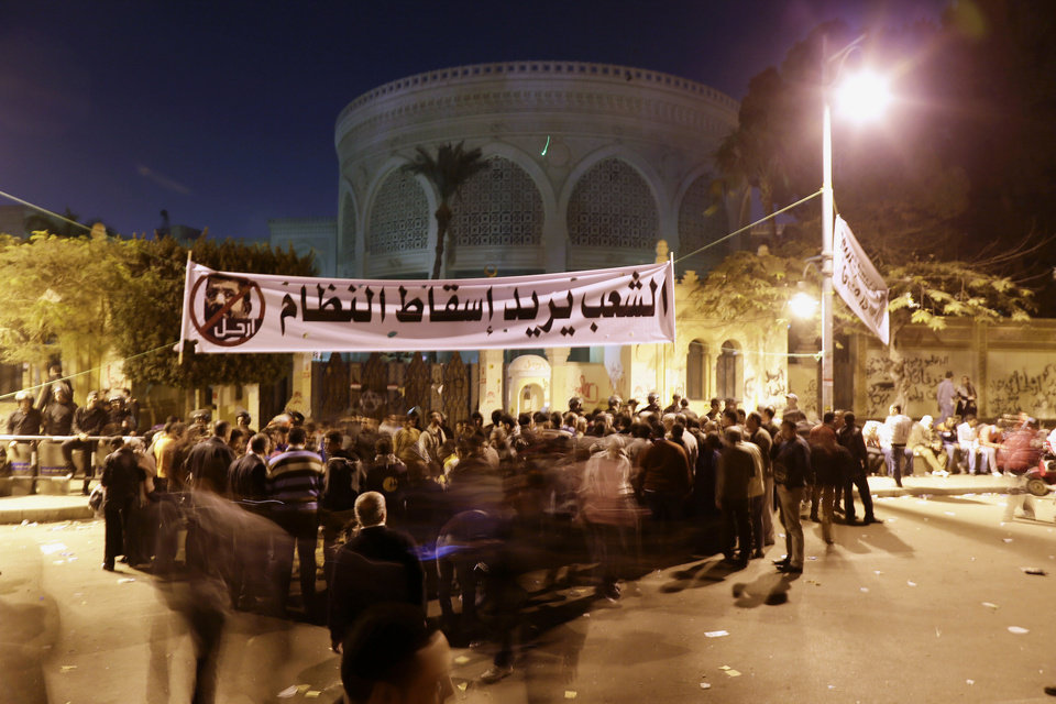 Egyptian protesters chant anti-Muslim Brotherhood and Egyptian President Mohammed Morsi slogans outside the presidential palace, background, under a banner with a defaced picture of President Mohammed Morsi and Arabic that reads