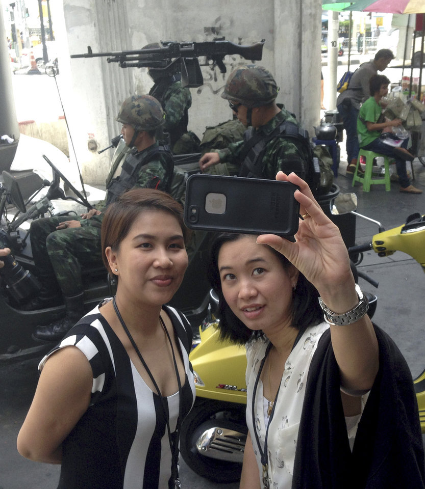 Photo - Residents stop to take a photograph of themselves at a military checkpoint in central Bangkok, Thailand, Tuesday, May 20, 2014. Thailand's army declared martial law in a surprise announcement before dawn Tuesday that it said was aimed at keeping the country stable after six months of sometimes violent political unrest. The military, however, denied a coup d'etat was underway. (AP Photo/Kiko Rosario)