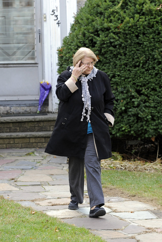 Photo - Erika Ilgenfritz  reacts after leaving flowers by the front door of the home where Richard Shoop lived in Teaneck, N.J. Tuesday Nov. 5, 2013.  Shoop fired multiple shots inside New Jersey's largest shopping mall Monday, trapping hundreds of customers and employees for hours as police scoured stores for the shooter, who was found dead early Tuesday of a self-inflicted wound, authorities said.   (AP Photo/Bill Kostroun)