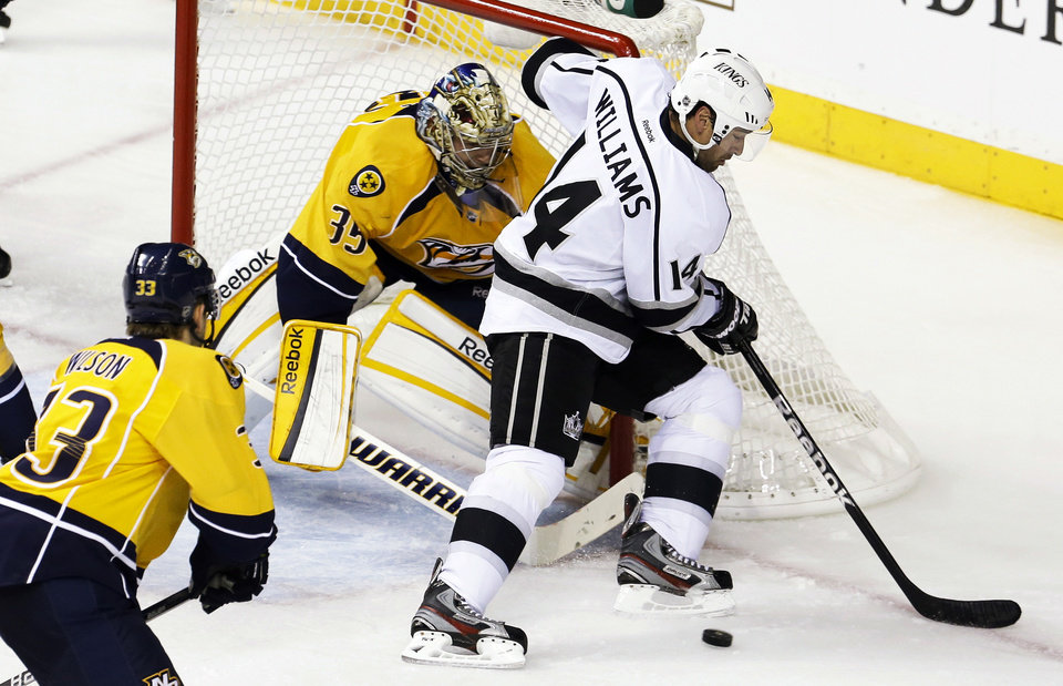 Photo - Nashville Predators goalie Pekka Rinne (35), of Finland, blocks the path of Los Angeles Kings right wing Justin Williams (14) in the second period of an NHL hockey game, Thursday, Feb. 7, 2013, in Nashville, Tenn. (AP Photo/Mark Humphrey)