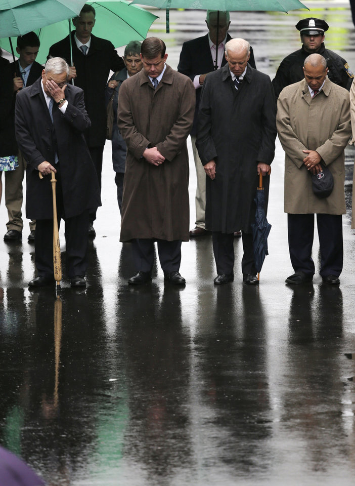 Photo - Former Boston Mayor Tom Menino, Boston Mayor Martin Walsh, Vice President Joe Biden and Mass. Gov. Deval Patrick lower their heads for a moment of silence during a tribute in honor of the one year anniversary of the Boston Marathon bombings, Tuesday, April 15, 2014 in Boston. (AP Photo/Charles Krupa)