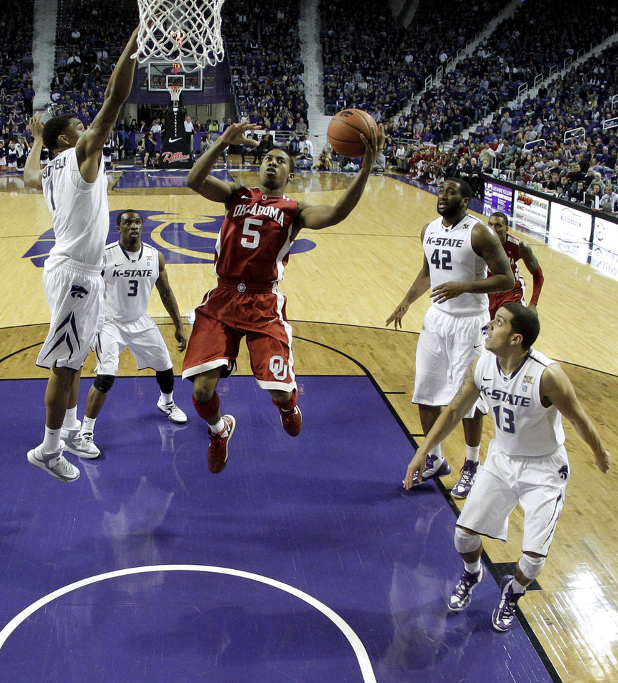 Oklahoma guard Je'lon Hornbeak (5) drives to the basket against Kansas State defenders during the first half of an NCAA college basketball game Saturday, Jan. 19, 2013, in Manhattan, Kan. (AP Photo/Charlie Riedel)