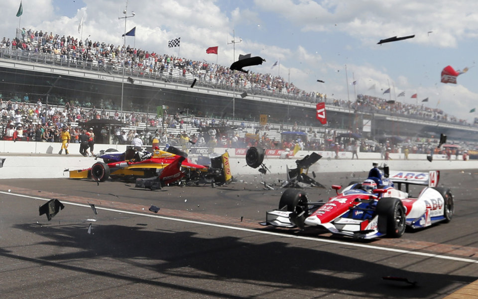 Photo - Sebastian Saavedra, left, of Colombia,  is hit by Mikhail Aleshin, of Russia, on the start of the inaugural Grand Prix of Indianapolis IndyCar auto race at the Indianapolis Motor Speedway in Indianapolis, Saturday, May 10, 2014. Takuma Sato, right, of Japan, drives past accident. (AP Photo/Robert Baker)