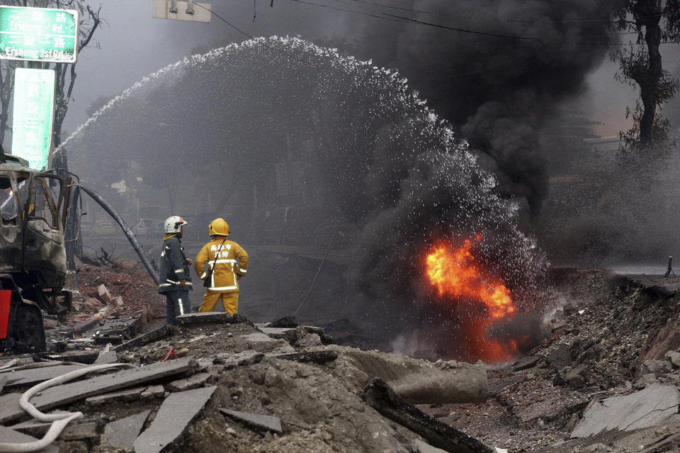Photo - Firemen put out fire on the part of a destroyed street as fire continue to burn following multiple explosions from an underground gas leak in Kaohsiung, Taiwan, early Friday, Aug. 1, 2014. Scores of people were killed and more than 200 others injured when several underground gas explosions ripped through Taiwan's second-largest city overnight, hurling concrete through the air and blasting long trenches in the streets, authorities said Friday. (AP Photo) TAIWAN OUT