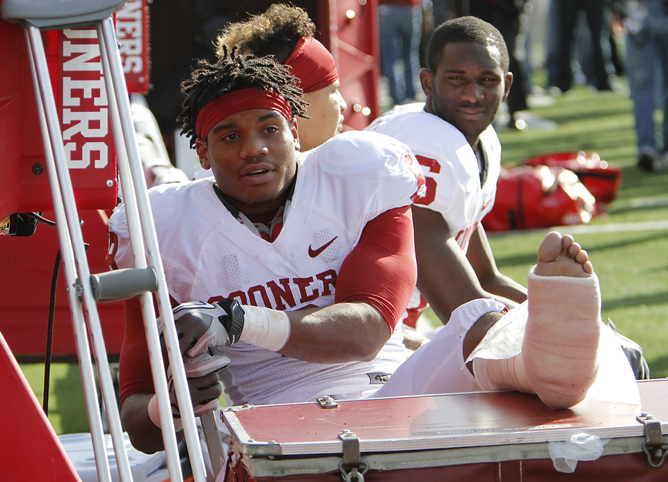 Photo - Oklahoma Sooners' Dominique Whaley (8) sits on the bench in a cast after bein injured on the first play of the game during the college football game between the University of Oklahoma Sooners (OU) and the Kansas State University Wildcats (KSU) at Bill Snyder Family Stadium on Sunday, Oct. 30, 2011. in Manhattan, Kan. Photo by Chris Landsberger, The Oklahoman  ORG XMIT: KOD