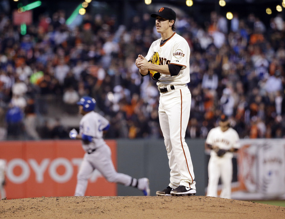 Photo - San Francisco Giants starting pitcher Tim Lincecum stands on the mound as Los Angeles Dodgers' Juan Uribe, left, rounds the bases on a solo home run in the second inning of a baseball game Tuesday, April 15, 2014, in San Francisco. (AP Photo/Marcio Jose Sanchez)