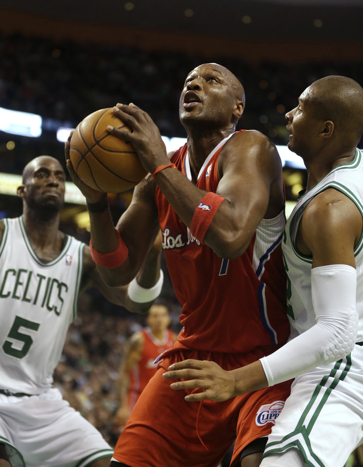 Photo - Los Angeles Clippers forward Lamar Odom, center, drives toward the basket while under pressure from Boston Celtics forward Kevin Garnett (5), left, and guard Leandro Barbosa, right, in the second quarter of an NBA basketball game at the TD Garden in Boston, Sunday, Feb. 3, 2013. (AP Photo/Steven Senne)