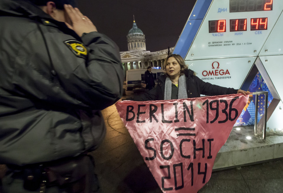 "Photo - A gay rights activist holds a banner in front of a large clock showing the number of days left until the start of the Olympic games as a police officer approaches, left, in St. Petersburg, Russia, Wednesday, Feb. 5, 2014. Russian gay rights activists protested the upcoming Olympic Games in Sochi. Two activists unfurled banners reading ""Berlin 1936 = Sochi 2014,"" referring to the Olympic Games that were held in the capital of Nazi Germany. One-man pickets are legal in Russia and the two activists holding signs were spaced far enough apart that neither was arrested. (AP Photo/Elena Ignatyeva)"