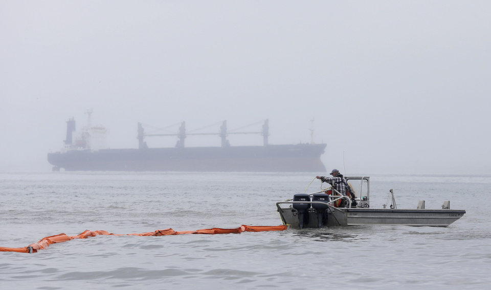 Photo - A boat drags an oil boom out into the water as a cargo ship sits in the ship waits to enter the ship channel along East Beach Monday, March 24, 2014, in Galveston, Texas.  The booms are being placed along the coastline to help clean up the thousands  of gallons of tar-like oil spilled into the major U.S. shipping channel after a barge ran into a ship Saturday. (AP Photo/Pat Sullivan)