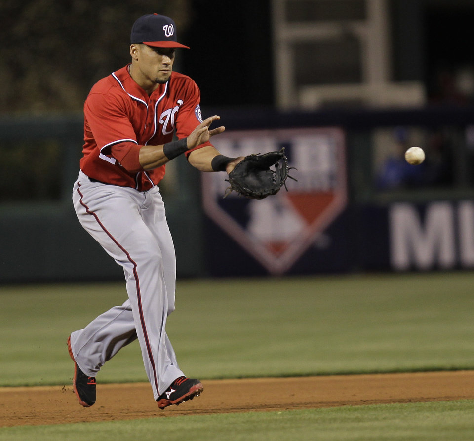 Photo - Washington Nationals' Ian Desmond fields a ball hit by Philadelphia Phillies A.J. Burnett and throws to first for an out in the fourth inning of a baseball game on  Saturday, May 3, 2014, in Philadelphia. (AP Photo/Laurence Kesterson)