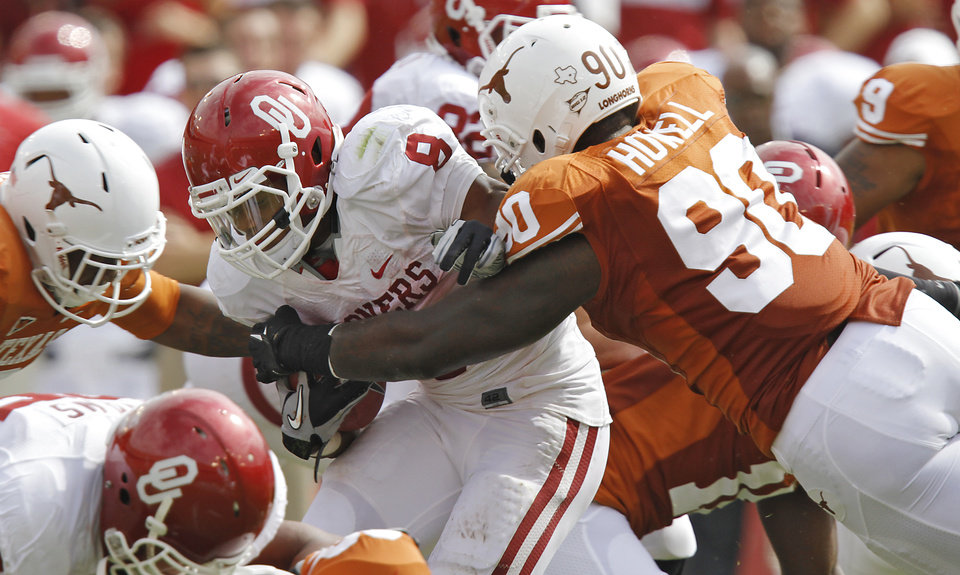 Oklahoma's Dominique Whaley (8) is stopped by Texas' Calvin Howell (90) during the Red River Rivalry college football game between the University of Oklahoma Sooners (OU) and the University of Texas Longhorns (UT) at the Cotton Bowl in Dallas, Saturday, Oct. 8, 2011. Photo by Chris Landsberger, The Oklahoman