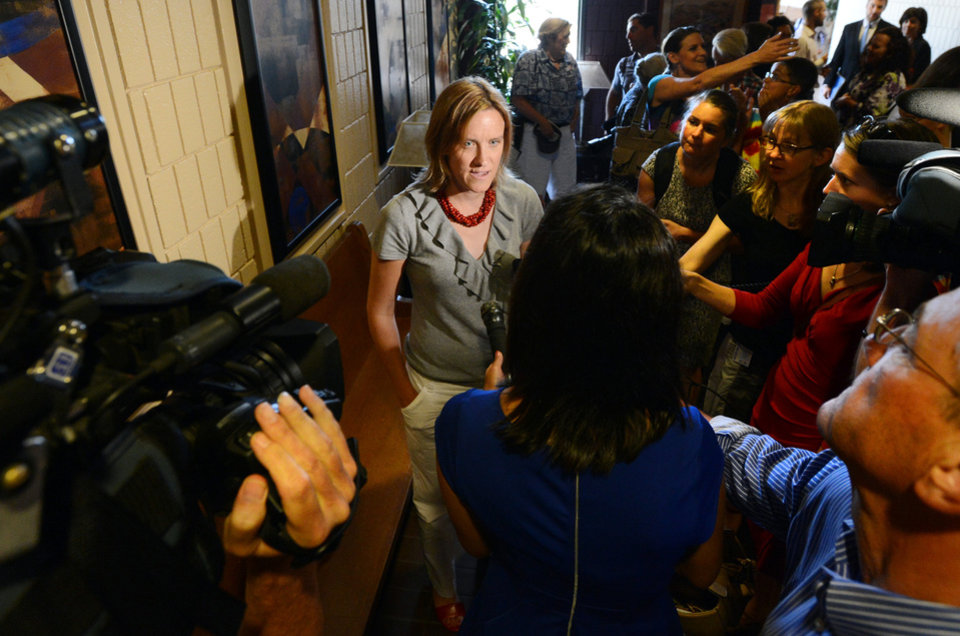 Photo - Samantha Frazee, a Longmont woman who has a civil union and received one of the 100 or so marriage licenses issued by Boulder County Clerk and Recorder Hillary Hall, talks to the media after a hearing at the Boulder County Justice Center on Wednesday, July 9, 2014. Hall is in court to respond to a suit brought by Colorado Attorney General John Suthers who wants the court to issue an injunction to stop the county from issuing marriage licenses to same-sex couples. (AP Photo/Daily Camera, Cliff Grassmick)