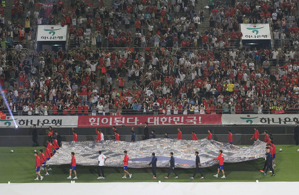 Photo - South Korea's national soccer team players carry a national flag during a send-off ceremony to the World Cup in Brazil after a friendly soccer match against Tunisian at World Cup stadium in Seoul, South Korea, Wednesday, May 28, 2014. South Korea will play against Belgium, Russia and Algeria in Group H of the World Cup 2014 in Brazil. (AP Photo/Ahn Young-joon)