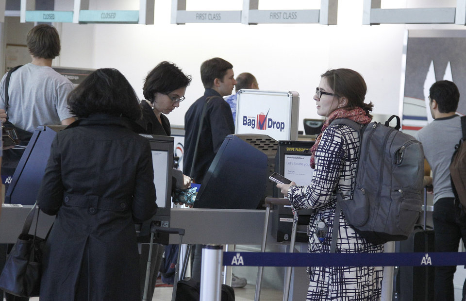 Photo -   Travelers line up at an American Airlines counter at Will Rogers Airport in Oklahoma City, Tuesday, Nov. 20, 2012, as travelers leave town for the Thanksgiving holiday. (AP Photo/Sue Ogrocki)