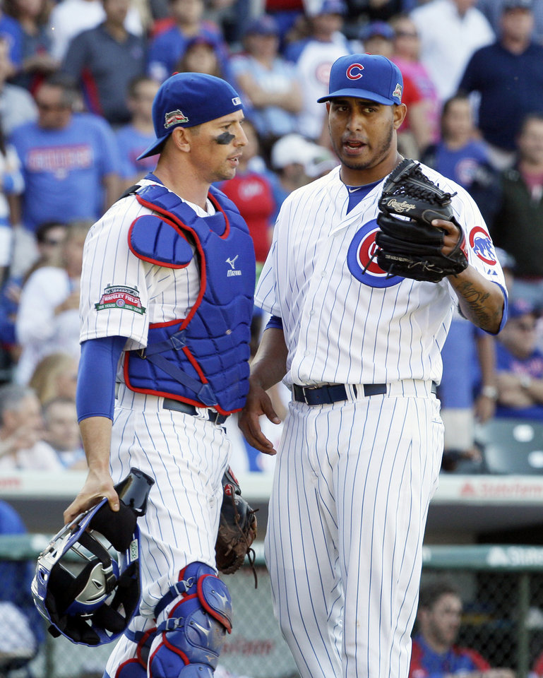 Photo - Chicago Cubs relief pitcher Hector Rondon, right, talks with catcher John Baker during the ninth inning of a baseball game against the Miami Marlins in Chicago, Friday, June 6, 2014. (AP Photo/Nam Y. Huh)