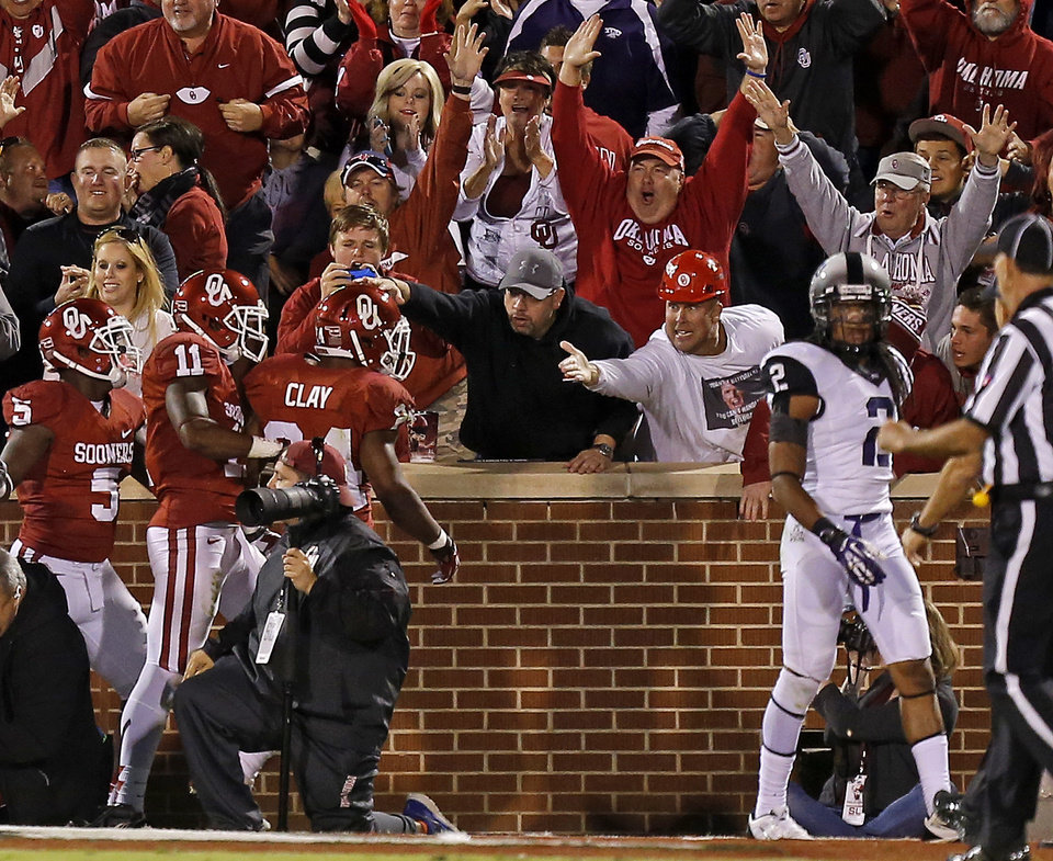 Photo - Fans celebrate with Oklahoma's Brennan Clay (24) after scoring beside TCU's Jason Verrett (2) during a college football game between the University of Oklahoma Sooners (OU) and the TCU Horned Frogs at Gaylord Family-Oklahoma Memorial Stadium in Norman, Okla., on Saturday, Oct. 5, 2013. Oklahoma won 20-17. Photo by Bryan Terry, The Oklahoman